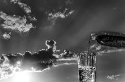 Gießen Sie Wasser in ein Glas auf dem Sonnenunterganghintergrund stockfoto
