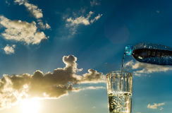 Gießen Sie Wasser in ein Glas auf dem Sonnenunterganghintergrund Lizenzfreies Stockbild