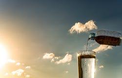 Gießen Sie Wasser in ein Glas auf dem Sonnenunterganghintergrund Stockfotos