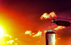 Gießen Sie Wasser in ein Glas auf dem Sonnenunterganghintergrund Lizenzfreie Stockbilder