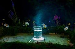 Gießen Sie Wasser in ein Glas auf dem Sonnenunterganghintergrund stockbild