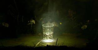 Gießen Sie Wasser in ein Glas auf dem Sonnenunterganghintergrund Lizenzfreie Stockfotos