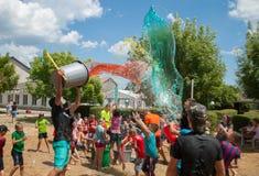 Gießen von Kindern durch Farbwasser, Sommerlager, Wasserfestival lizenzfreie stockfotos