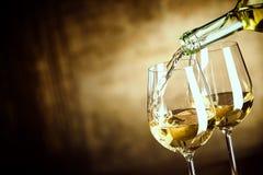 Gießen von zwei Gläsern Weißwein von einer Flasche Stockbild