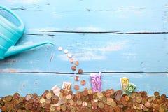 Gießkanne mit Euromünzen und Banknoten auf blauem Hintergrund, c Stockbild