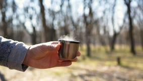 Gie?t hei?en Tee von einer Thermosflasche in eine Schale Picknick auf der Natur im Wald stock footage