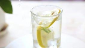 Gie?en eines Glases Wassers mit Zitrone, Eis und Minze auf einer wei?en Tabelle stock video