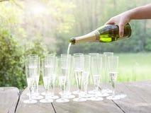 Gießen Sie Champagner während des Sonnenuntergangs Stockfotografie