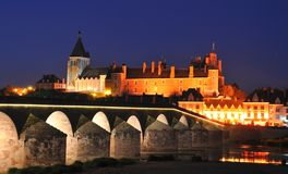 Gien bridge and castle. Scenic view of bridge over river Loire in town of Gien at night with Anne of Beaujeu's castle illuminated in background, Loiret, France Stock Photo