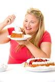 Gierige blonde Frau mit Mastsahnekuchen Lizenzfreie Stockfotografie