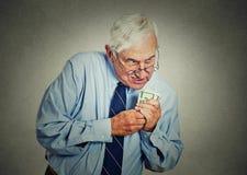 Gierige Exekutive, CEO, beherrschen den reifen Mann, der Dollarbanknoten hält Stockfotos