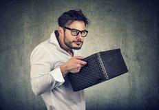 Gieriger junger Mann, der einen Kasten hält lizenzfreies stockfoto