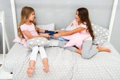 Gieriges Kinderkonzept Schwesterbeziehungsfragen Anteilbuch mit Freund Kinder im Schlafzimmer wünschen gelesen, Märchen glättend lizenzfreies stockfoto