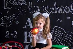 Gieriges Schulmädchen, das auf dem Schreibtisch mit Büchern, Schulbedarf, einen roten Apfel in der rechten Hand yholding sitzt lizenzfreies stockfoto