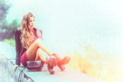 Gierl with long hair sitting on a low wall Stock Photo