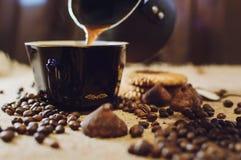 Giet de koffie in de kop Van koffiebonen en snoepjes achtergrond stock foto's