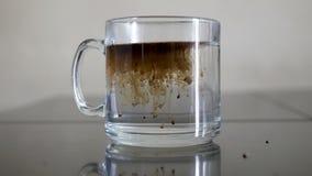 Giet de onmiddellijke koffie in warm water stock videobeelden