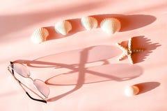 Giet de roze zonnebril van vrouwen met metaalkader een lange schaduw op de roze oppervlakte met seastar en zeeschelp royalty-vrije stock afbeeldingen