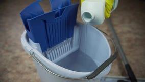 Giet detergens in de emmer om de ruimte schoon te maken stock videobeelden