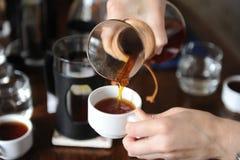Giet dicht omhoog vers gebrouwen koffie van een glaskruik op witte koppen royalty-vrije stock afbeeldingen