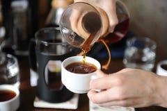 Giet dicht omhoog vers gebrouwen koffie van een glaskruik op witte koppen royalty-vrije stock fotografie