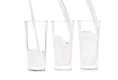 Giet een glas melk Stock Afbeeldingen