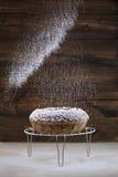 Giet gepoederde suiker op cake eigengemaakte ronde Royalty-vrije Stock Fotografie