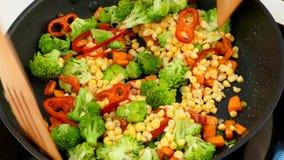 Giet graanpitten in een pan met gebraden groenten stock videobeelden