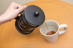 Giet koffie in koffiekop van koffiemachine Royalty-vrije Stock Afbeeldingen