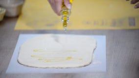 Giet olijfolie op het deeg stock footage