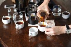 Giet vers gebrouwen koffie van een glaskruik op witte koppen stock foto
