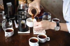 Giet vers gebrouwen koffie van een glaskruik op witte koppen stock fotografie