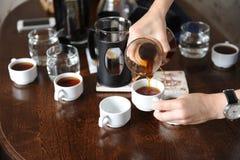 Giet vers gebrouwen koffie van een glaskruik op witte koppen royalty-vrije stock afbeeldingen