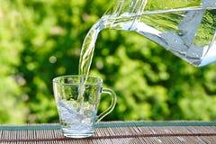 Giet water van een kruik in een glas stock fotografie