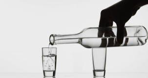 Gieten omhoog geschoten van wodka van een fles in glas Witte achtergrond stock afbeelding