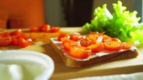 Gietend één of ander kruid en zettend een blad van groene salade op een sandwich, sluit omhoog stock video