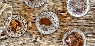 Gietend bier glazen met biertribune op een houten lijst Mening van hierboven close-up Royalty-vrije Stock Foto's