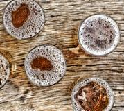 Gietend bier glazen met biertribune op een houten lijst Mening van hierboven close-up Royalty-vrije Stock Foto