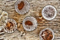 Gietend bier glazen met biertribune op een houten lijst Mening van hierboven close-up Royalty-vrije Stock Fotografie