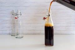 Gietend eigengemaakte koude brouw koffie van glaskruik aan glasfles stock foto