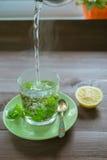 Gietend warm water bij de theemok met munt en een citroen op een donkere lijst Stock Foto