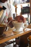 Gietend warm water in de filter van de koffiedruppel stock foto