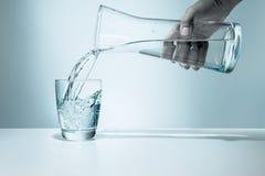 Gietend water in een glas stock foto's