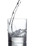 Gietend water in een glas op witte achtergrond royalty-vrije stock afbeelding
