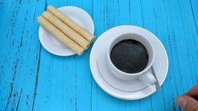 Gietend water en het maken van onmiddellijke koffie met zoete loempia's nabijgelegen stock footage