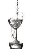 Gietend water in gebroken glas, op wit Stock Foto's