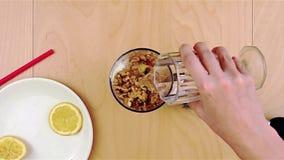 Gietend water over okkernoten in de mixer voor een gezonde en voedzame smoothie stock videobeelden