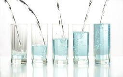 Gietend water in reeks van glas Stock Foto