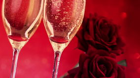 Gietende champagnefluiten met bellen dichtbij rode rozen op rode bokehachtergrond, liefde en valentijnskaartdag stock videobeelden