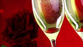 Gietende champagnefluiten met bellen dichtbij rode rozen op rood van de van de bokehconcept als achtergrond, liefde en valentijns stock video